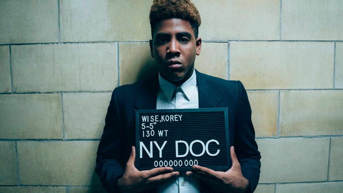 Fotograma en el que aparece Jharrel Jerome haciendo de Korey Wise con una placa de identificación en comisaría