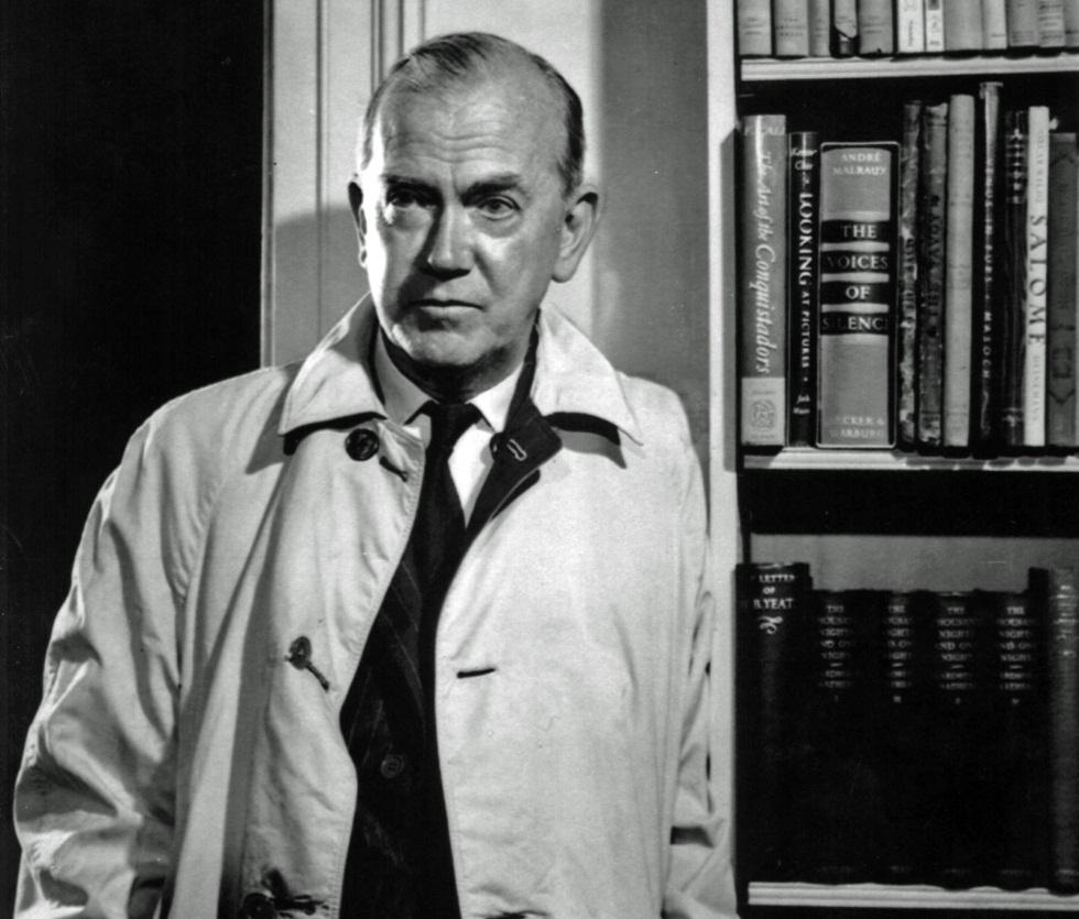 Retrato de Graham Greene con gabardina junto a una biblioteca