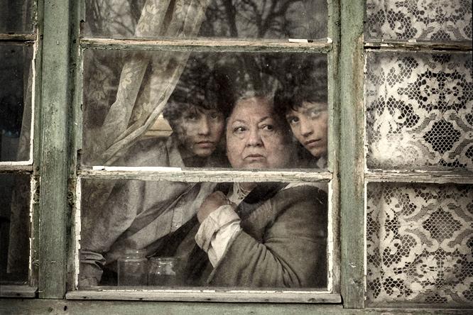 """La abuela y los gemelos asomados a una ventana. Fotograma de """"El gran cuaderno"""" (2013), de János Szász, adaptación de la obra de Agota Kristof"""